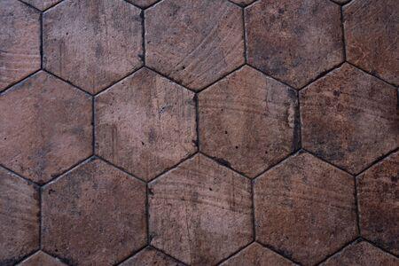 Vintage brown ceramic tile in the form of honeycombs. Hexagonal floor tiles.