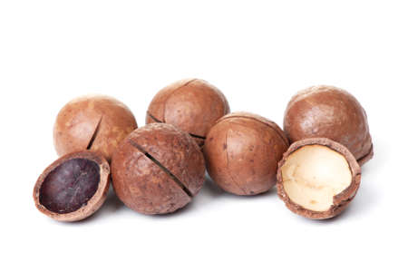 Heap of macadamia nut in shell isolated on white background