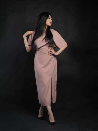 Asian woman model in long dress posing at studio over black background