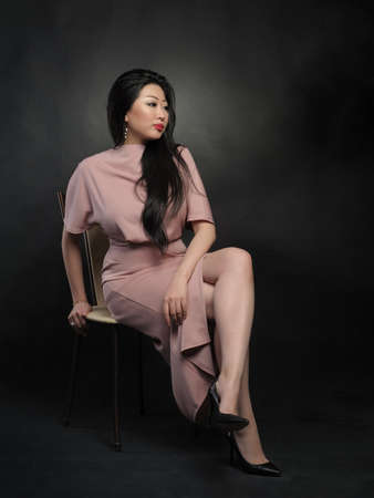 Asian woman model in long dress sitting and posing at studio over black background Stockfoto