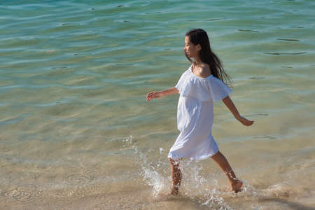 Young asian pregnant woman in a sundress in the water by the sea