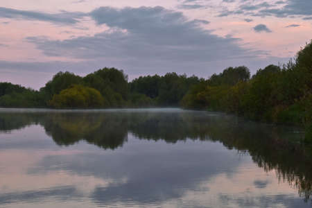 colorful and misty dawn over a small river