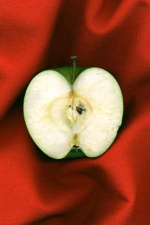 cintillos: la mitad de manzana verde sobre un fondo rojo Foto de archivo