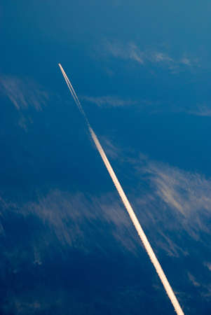 aeronautics: aircraft flying in the blue sky with clouds and a trace of it Stock Photo