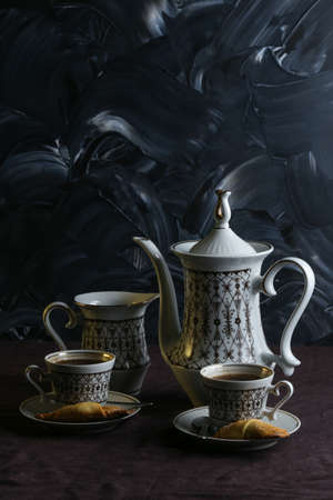 Coffee pot and cups with coffee on a table with a dark linen tablecloth with cookies on a dark background