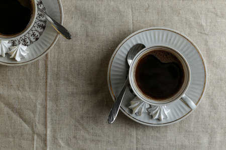 Coffee pot and cups with coffee on the table with a light linen tablecloth on a light background Stock fotó