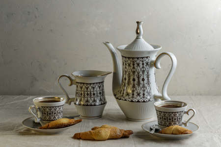 Coffee pot and cups with coffee on the table with a light linen tablecloth with cookies on a light background