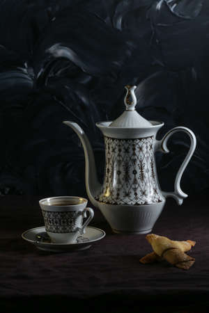 Coffee pot and cups with coffee on a table with a dark linen tablecloth on a dark background Stock fotó