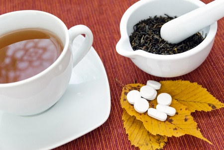 Picture of tea, herbs in mortar and pills for cold. photo