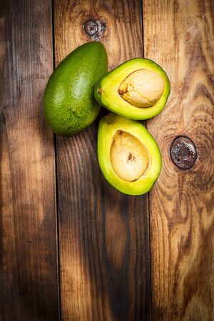Ripe avocado cut and lies on a wooden table Stock Photo