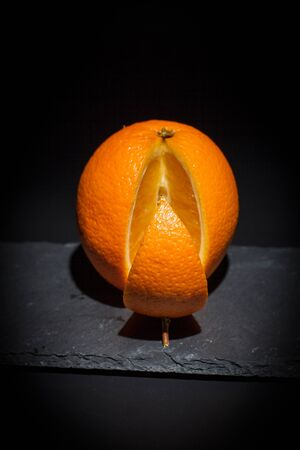 Sweet ripe orange on a black surface and black background