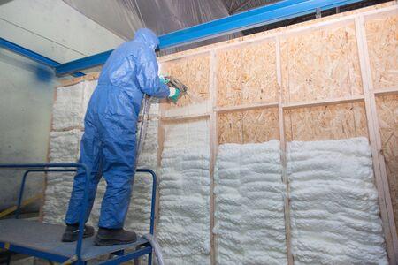 Worker foams the wall of a house Reklamní fotografie