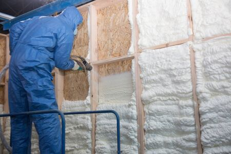Man insulates the walls with foam 免版税图像