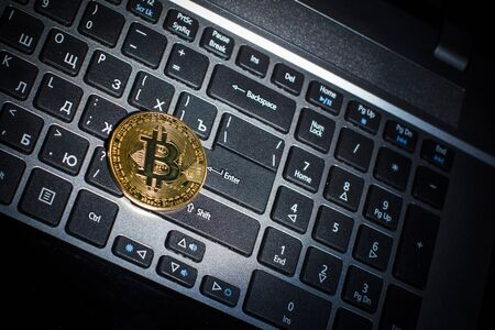 Golden bitcoin on laptop keyboard