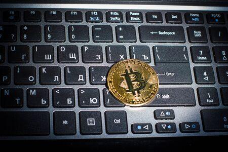 Golden bitcoin on laptop keyboard