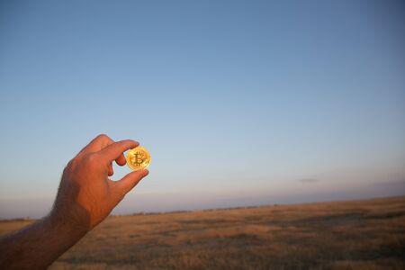 Man holds golden bitcoin at sunset