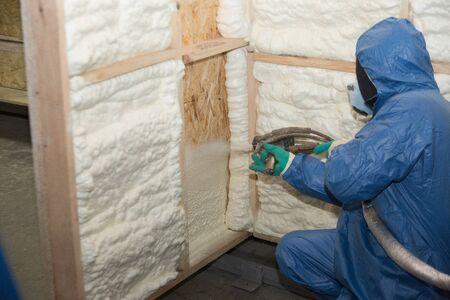 Werknemers isoleren muren met speciaal montageschuim Stockfoto