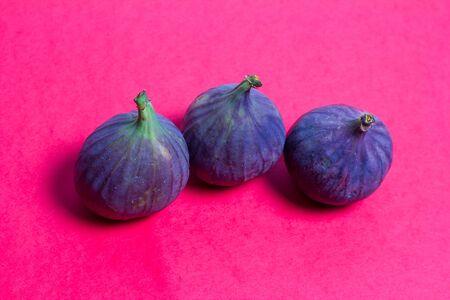 Ripe tasty figs on a red background Foto de archivo