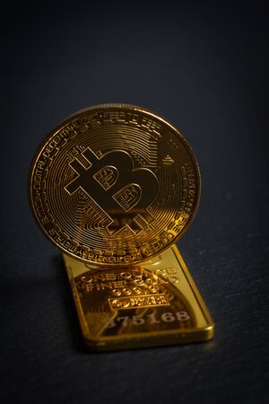 Bitcoins and gold bullion on black background close