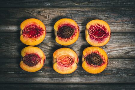 Ripe tasty peaches on a wooden brown surface in vintage style.