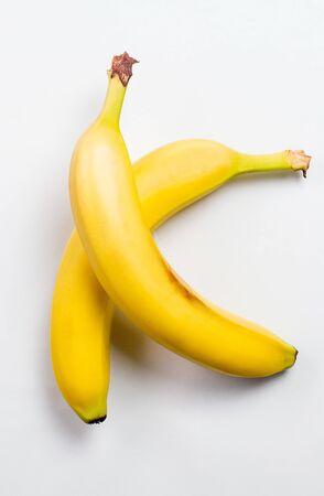 Plátanos amarillos frescos y sabrosos para una dieta saludable sobre un fondo blanco.