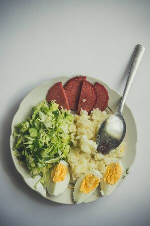 Plate with delicious breakfast with rice, sausage, eggs and salad close