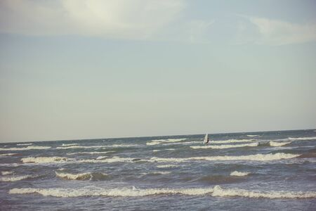 Athlete rides a sailing board at sea in a summer storm.