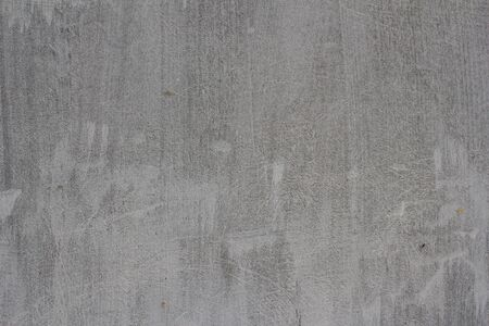 Gray concrete wall texture at a construction site with stripes and scratches and cracks.