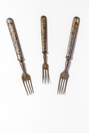 Antique metal rusty fork on a white background Imagens
