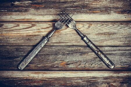Antique metal rusty fork on a vintage surface