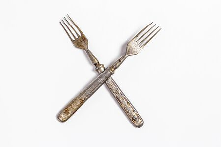 Antique metal rusty fork on a white background