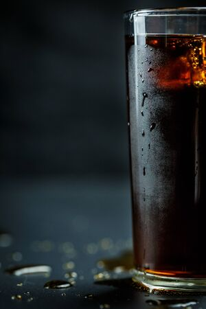Soda in a glass on a black background with ice cubes and drops close