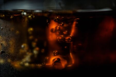 Soda in a glass on a black background with ice cubes and drops close Фото со стока