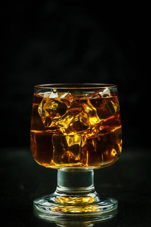 Glass with whiskey and ice cubes on a black background close