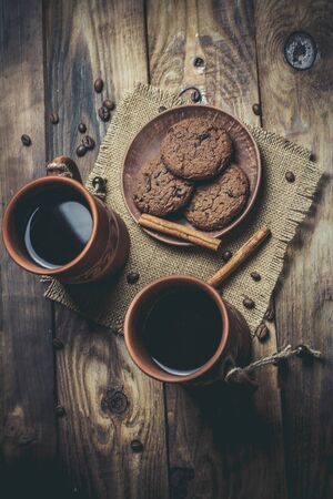 Brown clay vintage coffee mugs and delicious chocolate chip cookies on a wooden table in warm colors