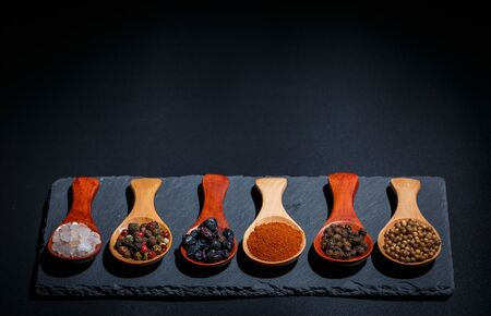 Different spices, peppers, coriander, sesame seeds and others for cooking are in wooden spoons on a black background