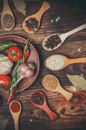 Diverse spezie in cucchiai di legno e diversi ingredienti per cucinare, pomodorini, aglio, coriandolo e peperoncino