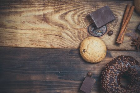 Chocolate donut and chocolate on a wooden table in warm color