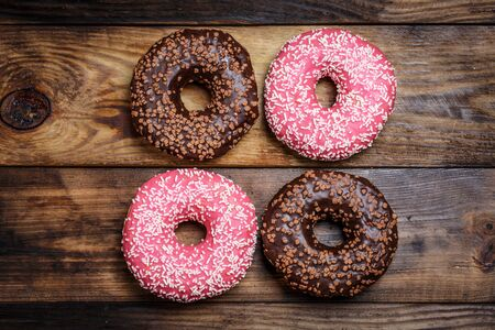 Chocolate and pink fresh donuts on a wooden breakfast table Stockfoto