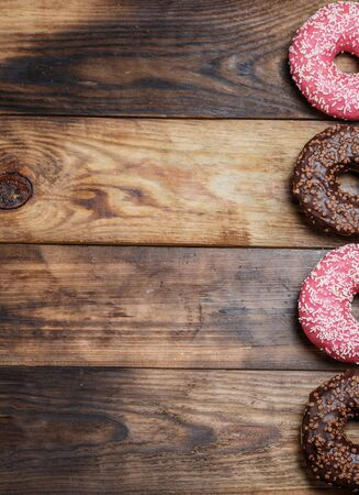 Chocolate and pink fresh donuts on a wooden breakfast table Banco de Imagens