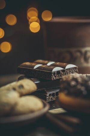 Delicious donuts with chocolate and a cup of coffee in warm colors. Banco de Imagens