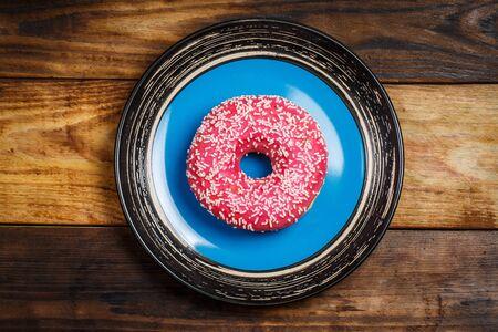 Tasty pink donut on a plate on wooden background Banco de Imagens