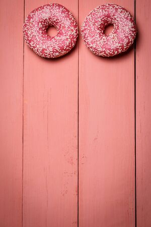 Tasty pink donut on a pink wooden background