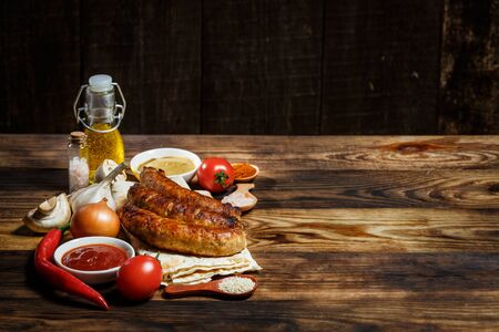 Grilled sausages, fresh vegetables, ingredients and spices on a wooden table