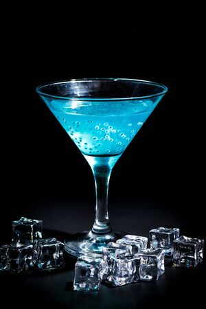 Aqua Menthe cocktail on a black background in a bar