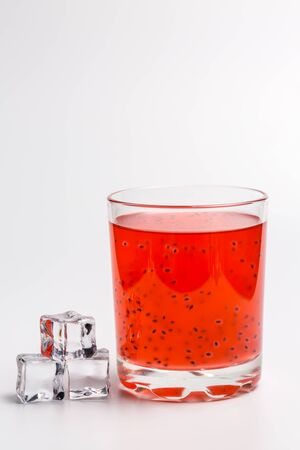 Tasty red cocktail with grains on a white background