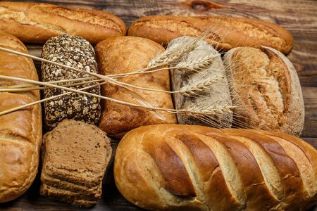 Different loaves of bread and rolls with wheat and flour on a wooden table