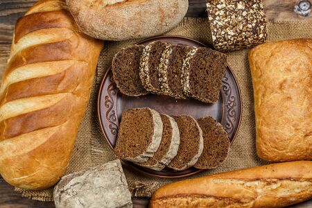 Fresh loaves of bread with wheat and gluten on a wooden table