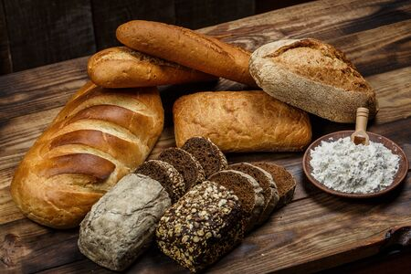 Different loaves of bread cooked with flour and gluten-free wheat on a wooden table