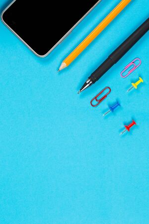 Different office supplies and tablet with a phone for work and education on a blue background Foto de archivo